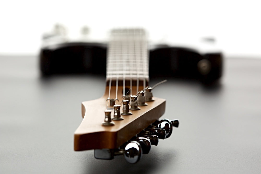 Electric guitar, fosuc view on head, closeup, nobody. String musical instrument, electro sound, electronic music, equipment for stage concert. Electric guitar, fosuc view on head, closeup