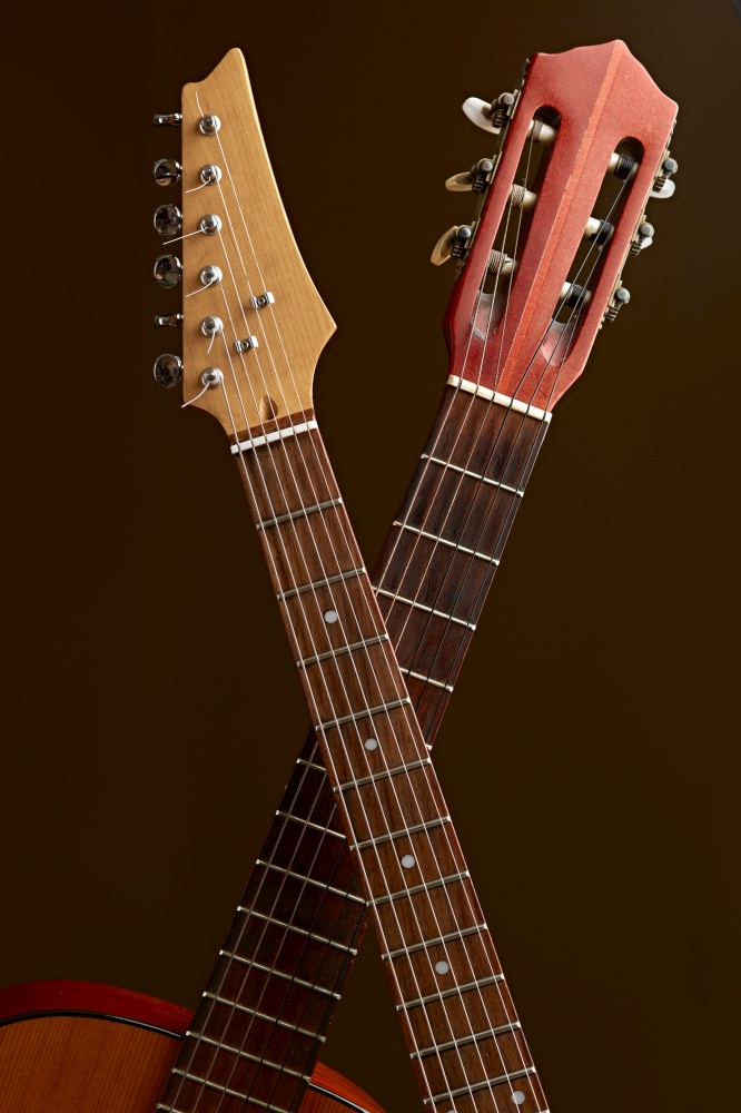 Modern electric and classical acoustic guitar fretboards closeup, brown background, nobody. String musical instrument, electro and live sound, music, equipment for musician. Electric and classical acoustic guitar fretboards
