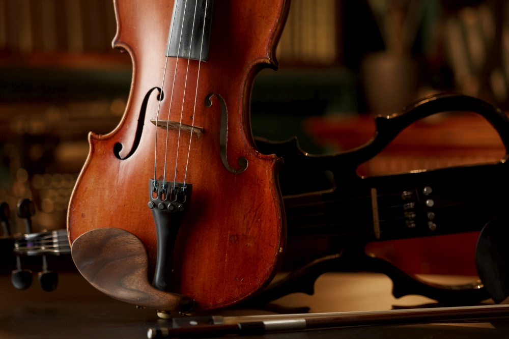Violin in retro style and modern electric viola, closeup view, nobody. Two classical string musical instruments, music art, dark background. Violin in retro style and electric viola, closeup
