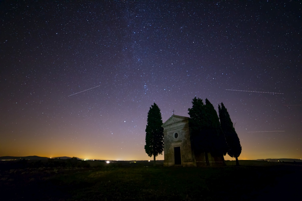 Italy. Tuscany. Lonely chapel and cypress trees in a field. Night sky with myriads of stars. Starry Sky over Church