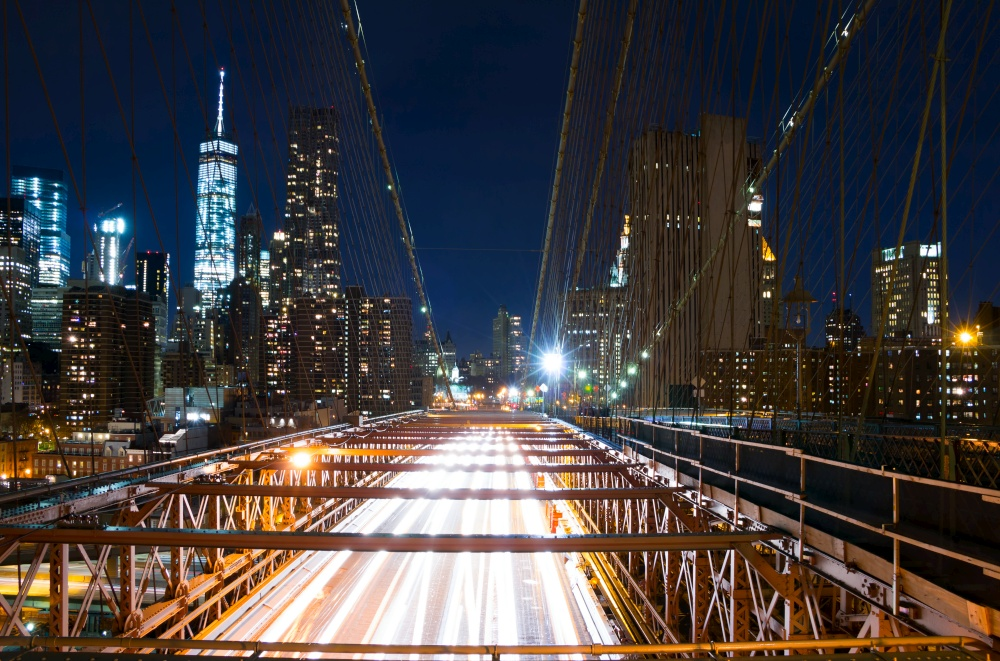 USA. New York City. Night Brooklyn bridge. View of the traffic on the bridge and the skyscrapers of Manhattan. Brooklyn Bridge at Night